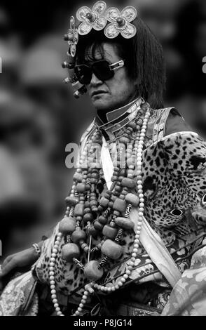 Male Khampa wears leopard skin, coral, zee stones & gold gau boxes at the Litang Horse Festival - Sichuan Province, China, (Tibet) - Stock Photo