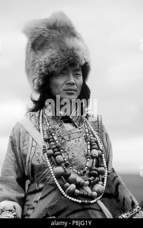 Male Khampa wears coral, zee stones, fox fur hat & tiger skin at the Litang Horse Festival - Sichuan Province, China, (Tibet) - Stock Photo
