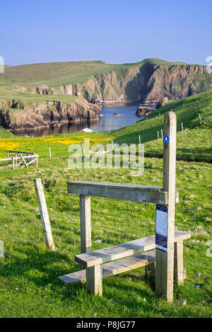 Wooden stile crossing on fence along the spectacular coastline with sea cliffs and stacks at Westerwick, Mainland, Shetland Islands, Scotland, UK - Stock Photo