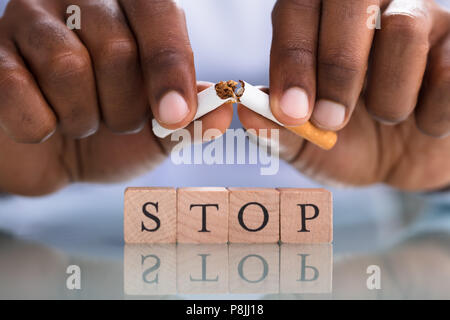 Close-up Of A Person's Hand Breaking Cigarette Over The Stop Blocks On The Reflective Desk - Stock Photo