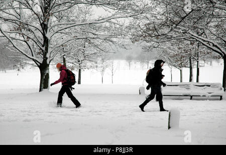People walking through the snow in Regents Park, NW London, England, UK - Stock Photo