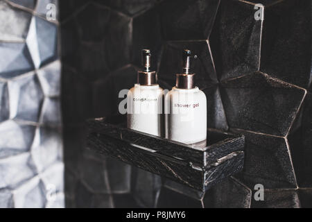 Two white metal bottles of conditioner, shower gel on wooden shelf  in modern hotel bathroom with textured black wall - Stock Photo