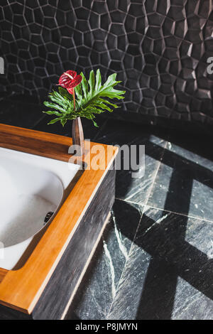 Modern design of bathroom with textured black tile and walls, wooden edge of bathtub. Light from window and flower pot - Stock Photo