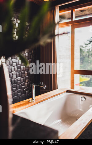 Modern bathroom with black walls, wooden decoration and big panoramic window - Stock Photo