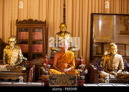 An elderly male monk meditating in a temple in Thailand. - Stock Photo
