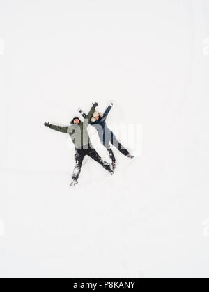 Aerial image of a happy couple having fun on white now - Stock Photo