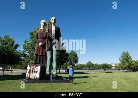 A tourist looking at Seward Johnson's 25 foot statue 'God Bless America' in Elkhart Indiana's Central Park. It is a 3-dimensional re-creation of the i - Stock Photo