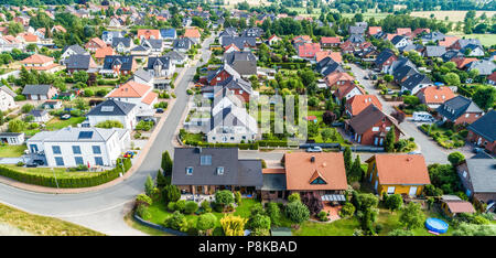 Typical German new housing development in the flat countryside of northern Germany between a forest and fields and meadows, made with drone - Stock Photo