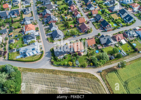 Typical German new housing development in the flat countryside of northern Germany between fields and meadows, made with drone - Stock Photo