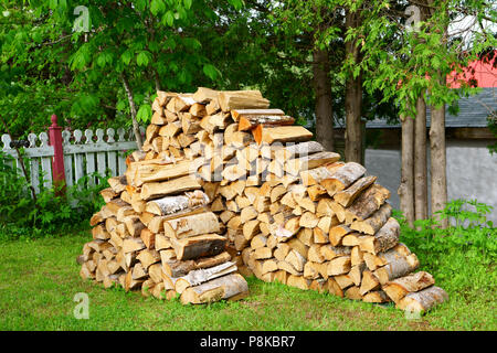 A pile of split logs in the backyard ready for a cold winter in order to heat the house. - Stock Photo