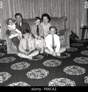1950s, famliy at home, mother and father with their three boys and young infant sitting togetther on the sofa in their living room which has a distinctive patterned carpet. - Stock Photo