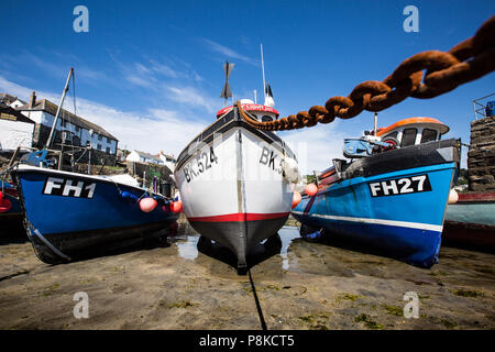 Traditional Cornish fishing boats that are beached and waiting for the tide to come in on the sand of Coverack harbour in Cornwall, UK. - Stock Photo