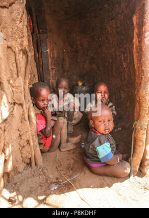 Unknown Masai village near Amboselli park, Kenya - April 02, 2015: Group of poor dirty children with faces and mouth covered with flies sitting at ent - Stock Photo