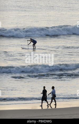 Virginia Beach, VA-August 31, 2017: Man on paddle board paddles in the surf of the ocean at Virginia Beach, VA. - Stock Photo