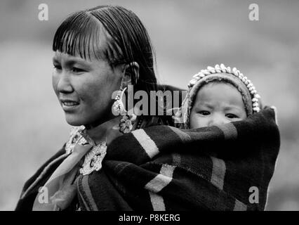 WOMAN and CHILD in DOLPO BLANKET and silver clasp at a Tibetan Buddhist FESTIVAL in DO TARAP VALLEY - DOLPO, NEPAL - Stock Photo