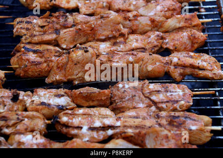 Chicken Kebabs cooking on a grill - Stock Photo