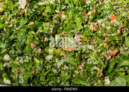 A tray of Tabbouleh salad, a Middle Eastern vegetarian salad - Stock Photo