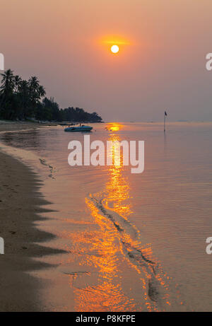 A colorful sunset on the island of Koh Samui in Thailand. - Stock Photo