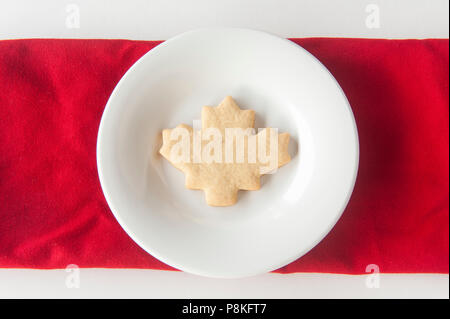 One maple leaf shaped cookie on a round white plate - Stock Photo