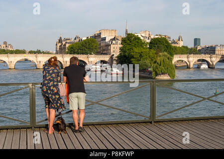 Paris, 24 June 2018: Tourists enjoying the view from Pont des Arts bridge. - Stock Photo