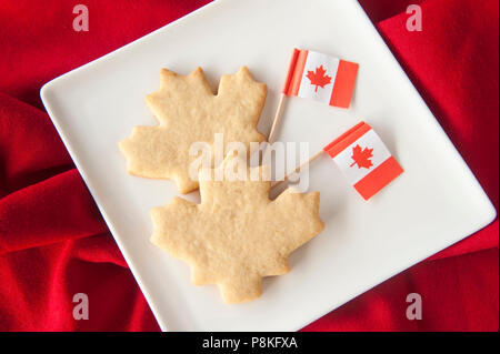 Two maple leaf shaped cookies on a plate with Canadian flags on red - Stock Photo