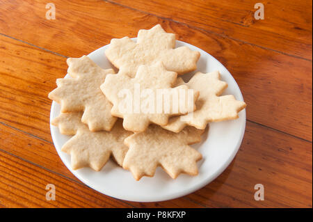 Plate of plain leaf shaped cookies on a round white plate on a wooden table - Stock Photo