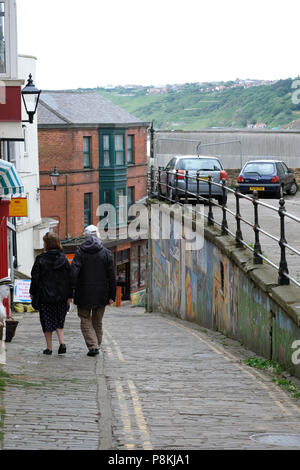 Elderly couple walking down the steep drop of Bland's Cliff,Scarborough,UK past the shops and street art to the sea front in the distance - Stock Photo