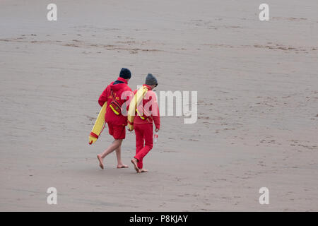 Two lifeguards patrol the beach on South Bay, Scarborough, Yorkshire, England,UK - Stock Photo