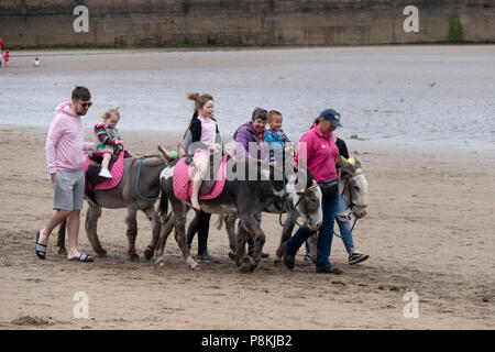 Holiday makers and families having fun  with donkeys on the beach at South Bay in the North Yorkshire holiday resort of Scarborough,UK - Stock Photo