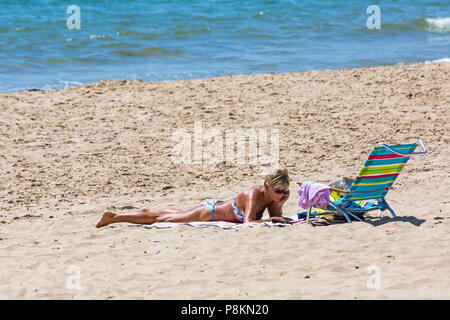 Bournemouth, Dorset, UK. 12th July 2018. UK weather: The heatwave continues with another hot sunny day, as sunseekers make the most of the glorious weather and head to the seaside at Bournemouth beaches.  Woman in bikini sunbathing. Credit: Carolyn Jenkins/Alamy Live News - Stock Photo