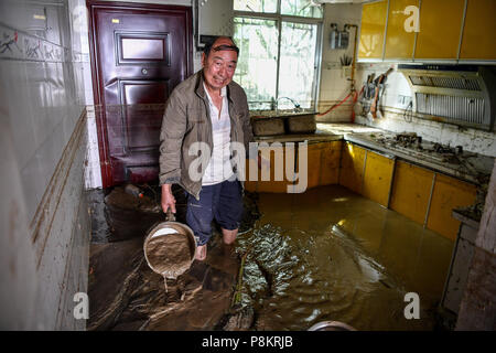 Beichuan, China's Sichuan Province. 12th July, 2018. A villager clears the mud at home after the flood in Chenjiaba Town of Beichuan County, southwest China's Sichuan Province, July 12, 2018. Lasting torrentials in the past days have caused severe flood in Santai, Beichuan and Pingwu counties in Sichuan. 595 flood-stranded people at Laochang Village of Chenjiaba Town have been evacuated. Credit: Zhang Chaoqun/Xinhua/Alamy Live News - Stock Photo