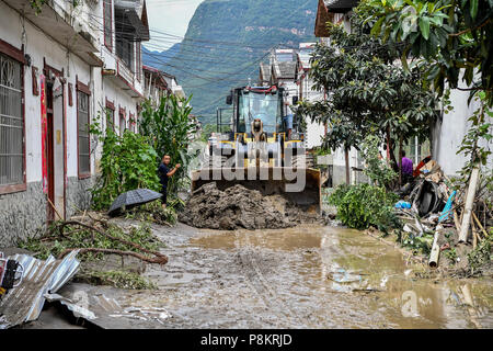 Beichuan, China's Sichuan Province. 12th July, 2018. People clear mud on the street in Chenjiaba Town of Beichuan County, southwest China's Sichuan Province, July 12, 2018. Lasting torrentials in the past days have caused severe flood in Santai, Beichuan and Pingwu counties in Sichuan. 595 flood-stranded people at Laochang Village of Chenjiaba Town have been evacuated. Credit: Zhang Chaoqun/Xinhua/Alamy Live News - Stock Photo