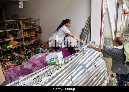 Beichuan, China's Sichuan Province. 12th July, 2018. A villager sends out bottles of mineral water to her neighbors in Chenjiaba Town of Beichuan County, southwest China's Sichuan Province, July 12, 2018. Lasting torrentials in the past days have caused severe flood in Santai, Beichuan and Pingwu counties in Sichuan. 595 flood-stranded people at Laochang Village of Chenjiaba Town have been evacuated. Credit: Zhang Chaoqun/Xinhua/Alamy Live News - Stock Photo