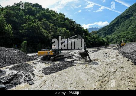 Beichuan, China's Sichuan Province. 12th July, 2018. A river is cleaned up in Chenjiaba Town of Beichuan County, southwest China's Sichuan Province, July 12, 2018. Lasting torrentials in the past days have caused severe flood in Santai, Beichuan and Pingwu counties in Sichuan. 595 flood-stranded people at Laochang Village of Chenjiaba Town have been evacuated. Credit: Chen Di/Xinhua/Alamy Live News - Stock Photo