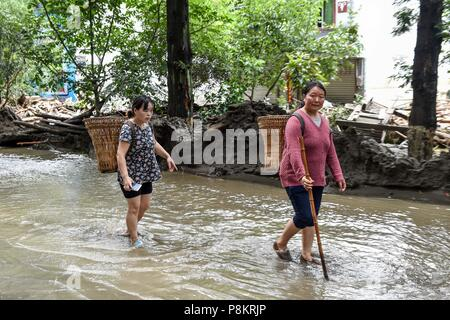 Beichuan, China's Sichuan Province. 12th July, 2018. Villagers wade through water on the street after the flood in Chenjiaba Town of Beichuan County, southwest China's Sichuan Province, July 12, 2018. Lasting torrentials in the past days have caused severe flood in Santai, Beichuan and Pingwu counties in Sichuan. 595 flood-stranded people at Laochang Village of Chenjiaba Town have been evacuated. Credit: Chen Di/Xinhua/Alamy Live News - Stock Photo
