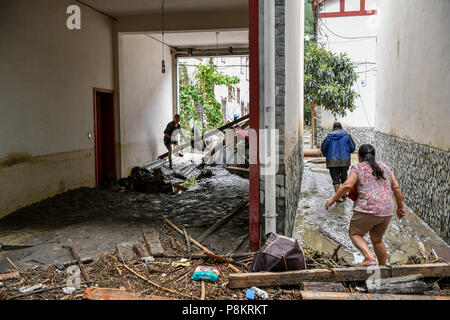 Beichuan, China's Sichuan Province. 12th July, 2018. Flood victims go back home after the flood in Chenjiaba Town of Beichuan County, southwest China's Sichuan Province, July 12, 2018. Lasting torrentials in the past days have caused severe flood in Santai, Beichuan and Pingwu counties in Sichuan. 595 flood-stranded people at Laochang Village of Chenjiaba Town have been evacuated. Credit: Zhang Chaoqun/Xinhua/Alamy Live News - Stock Photo