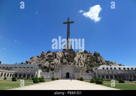 FILED - 05 July 2018, Spain, El Escorial: A 155 metres high and 44 metres wide concrete cross stands on the top of the Risco de la Nava behind the Benedictine abbey in the Valle de los Caidos (Valley of the Fallen). Inside the monument next to Cuelgamuros near El Escorial in the Sierra de Guadarrama lies the tomb of Spanish dictator Francisco Franco and the founder of the fascist movement Falange, José Antonio Primo de Rivera. It is known as one of the largest newer mausoleums of the world and the most important architectural symbol of Franco's dictatorship. Next to the basilica, in a shrine, - Stock Photo