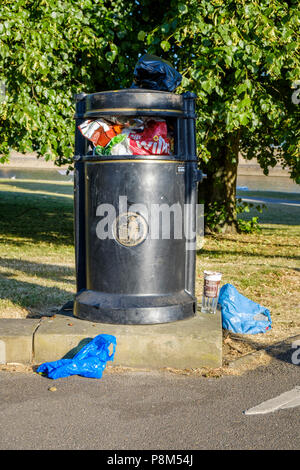 Full litter bin overflowing with rubbish on top and around it on the ground, Nottinghamshire, England, UK - Stock Photo