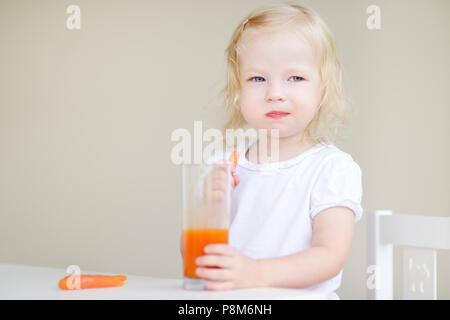 Adorable toddler girl eating carrots and drinking carrot juice - Stock Photo