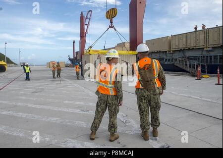 Sailors assigned to Navy Cargo Handling Battalion (NCHB) 1, Det, July 2, 2018. Guam, on load ammo cans to a cargo ship at Naval Base Guam, July 2, 2018. NCHB 1 Det. Guam, assigned to Commander, Task Force 75, is the Navy's only active duty cargo handling battalion, and is a rapidly deployable operating unit of the Navy Expeditionary Combat Command, capable of loading and discharging ships and aircraft in all climatic and threat conditions. (U.S. Navy photo by Mass Communication Specialist 3rd Class Kryzentia Richards). () - Stock Photo
