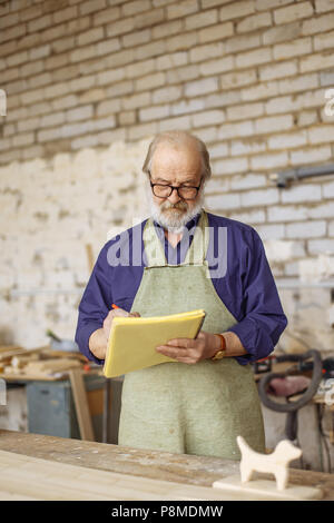 nice pensioner in glasses is drawing a graph in the home workshop. closeup photo. small business - Stock Photo