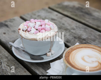 A luxury hot chocolate drink in a posh cup and saucer with whipped cream and marshmallows melting and dribbling down the cup - Stock Photo
