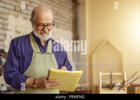 attractive old carpenter working on designs in his workshop.close up photo. write down the plan of work - Stock Photo