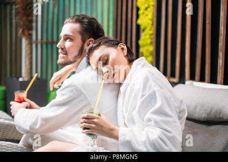 close up photo of beautiful girl putting her head on her boyfriend's shoulder in the spa salon