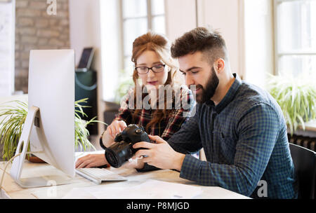Two young designers working in modern office - Stock Photo