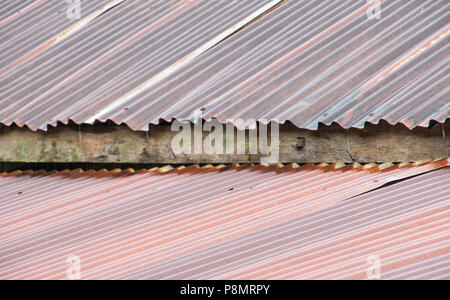 Old rusty galvanized roof during raining - Stock Photo