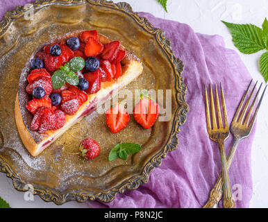 half cheesecake with strawberries on an iron copper plate and two forks, top view - Stock Photo
