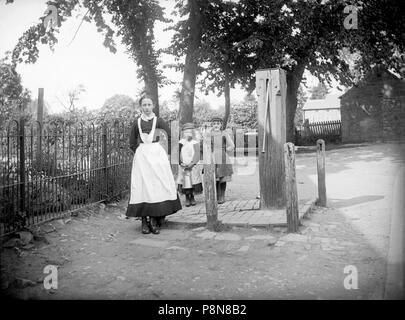 Village pump, Grandborough, Warwickshire, 1901. A young servant girl has been sent to fetch water from the village pump. Two urchins are on a similar  - Stock Photo