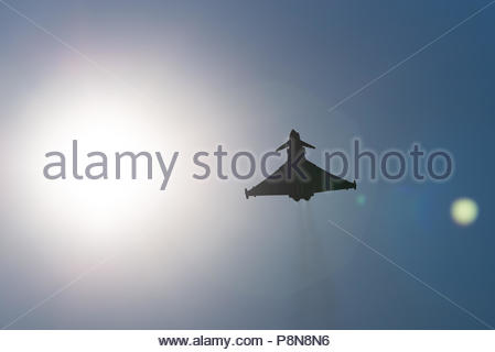 An image of a RAF Typhoon Euro Fighter in flight, artistically photographed into the sun to create lens flare and a silhouette - Stock Photo