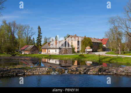 Old rural farmhouses near a pond at summer day - Stock Photo